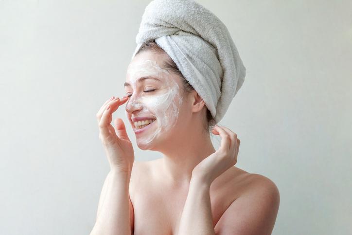 Eine junge Frau cremt sich ihr Gesicht ein, damit die Faltenbildung reduziert wird.