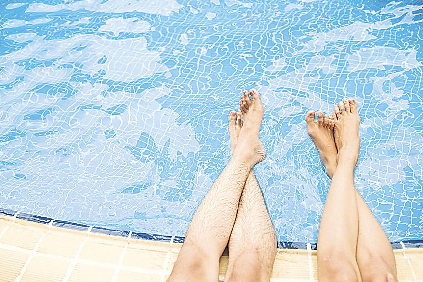 Füße über einem Schwimmbeckenrand. Dort verbreitet sich Nagelpilz besonders häufig.