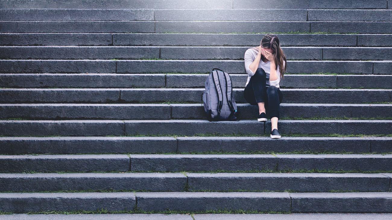 Ein Mädchen sitzt traurig auf einer Treppe. Thema: Neurodermitis bei Jugendlichen
