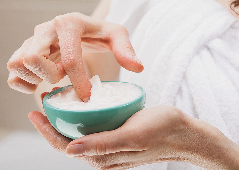Jemand steckt einen Finger in einen Cremetiegel. Thema: Basispflege der Haut