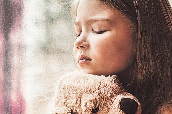 Mädchen mit Teddy im Arm an Fensterscheibe; Thema: Arten von Psoriasis