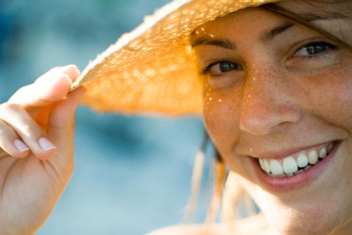 Frau mit Sonnenhut blickt in die Kamera