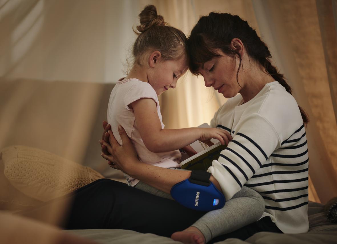 Mutter und Kind mit dem Lichttherapie-Gerät gegenPsoriasisvon Philips