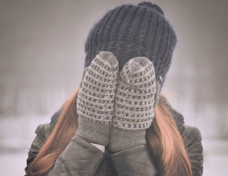 Ein Mädchen versteckt ihr Gesicht mit Handschuhen; Thema: Winter-Akne
