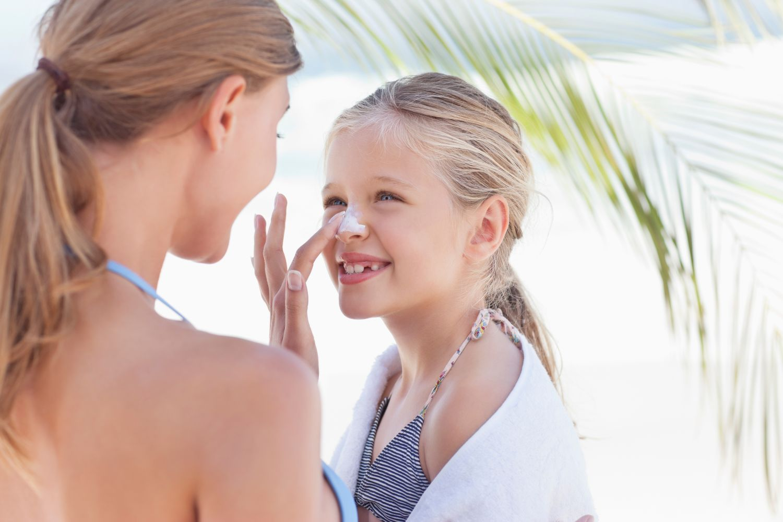 Mutter cremt ihr Kind mit Sonnenmilch ein. Thema: Sonnenbaden