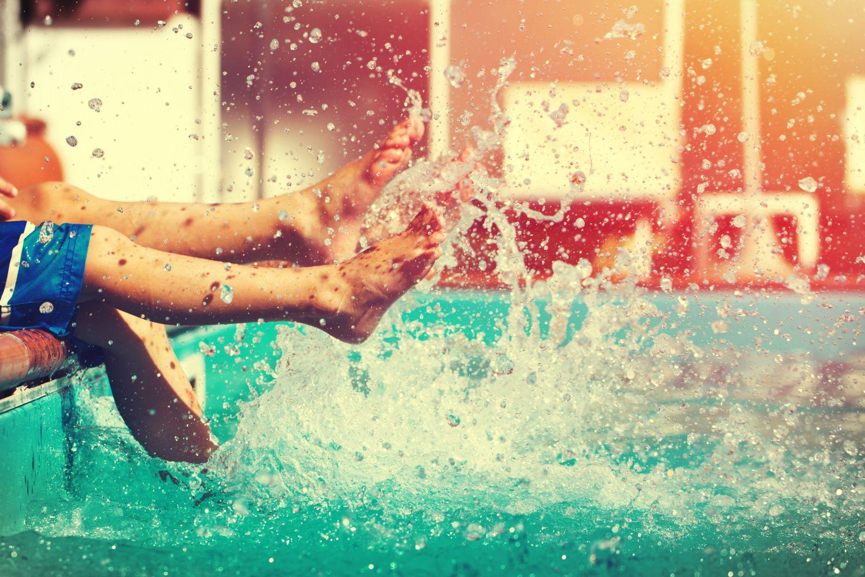 Planschende Füße im Freibad, wo Warzen schneller übertragen werden