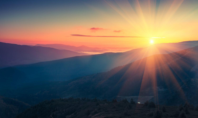 Berglandschaft im Sonnenaufgang. Zu viel Sonneneinstrahlung sollte man meiden - um sich vor Hautkrebs zu schützen.
