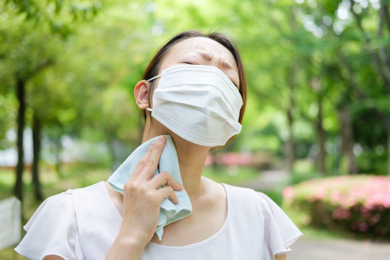 Eine Frau schwitzt unter ihrer Gesichtsmaske. Das verschlimmert die Rosazea im Sommer.