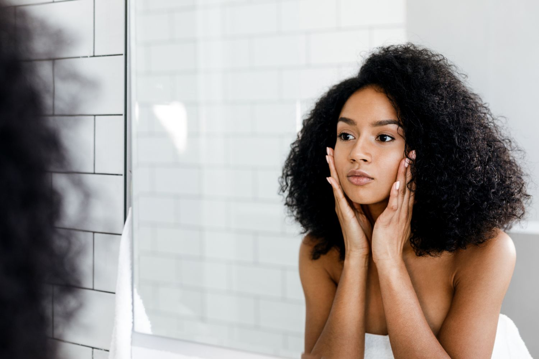 Eine Frau schaut in einen Spiegel. Thema: Funktionen der Haut
