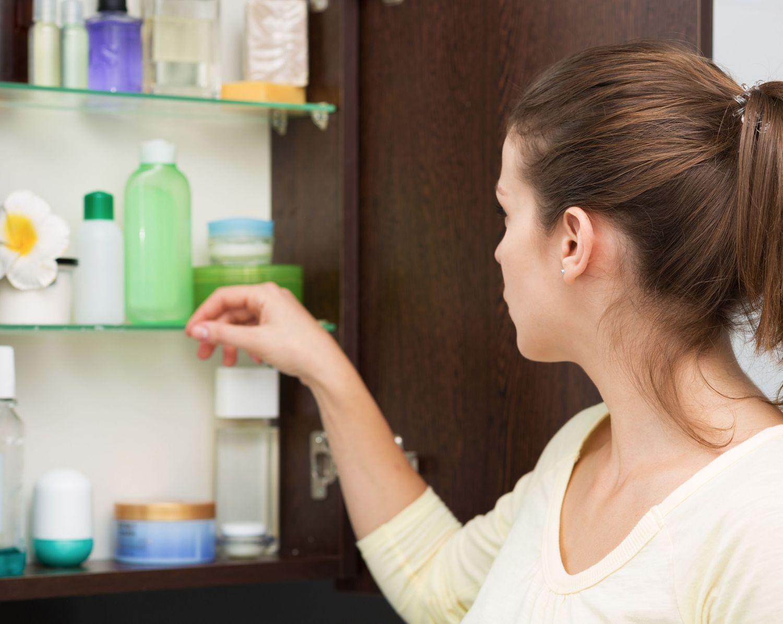 Vor ihrem Badschrank sucht sich eine Frau Kosmetikprodukte aus. Thema: Juckreiz
