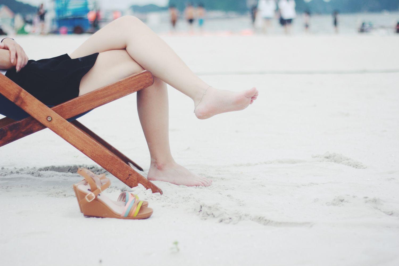 Strandszene mit einer Person im Liegestuhl. Thema: Pilzinfektion