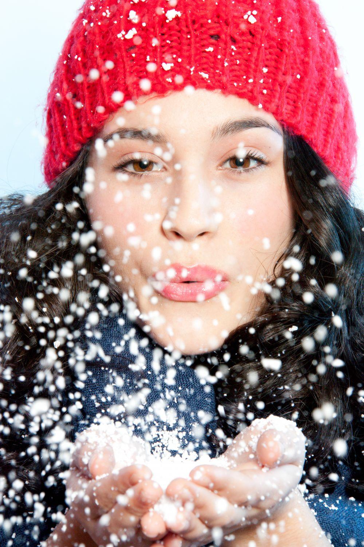 Frau bläst Schnee von ihrer Hand