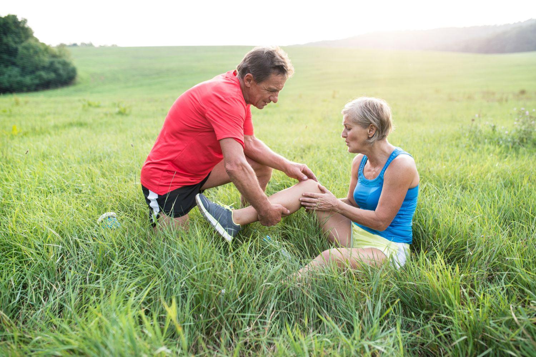 Senioren auf einer Wiese; Seniorin mit Schmerzen im Knie. Thema: Psoriasisarthritis