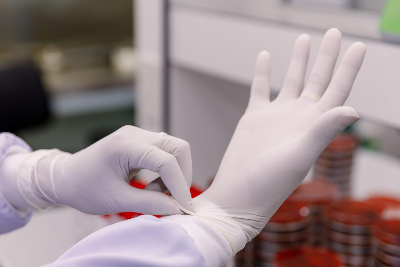 Jemand zieht sich Latexhandschuhe an. Thema: Provokationsfaktoren bei Neurodermitis