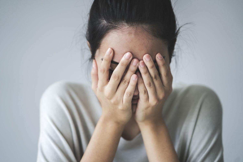 Eine Frau versteckt ihr Gesicht und ihren Händen. Thema: Folgeerkrankungen bei Psoriasis