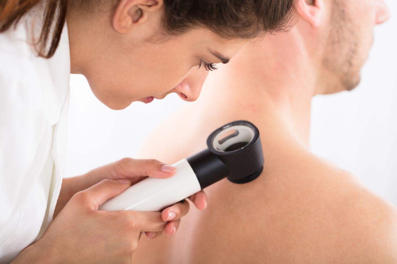 Ärztin untersucht Patienten auf Hautkrankheiten.