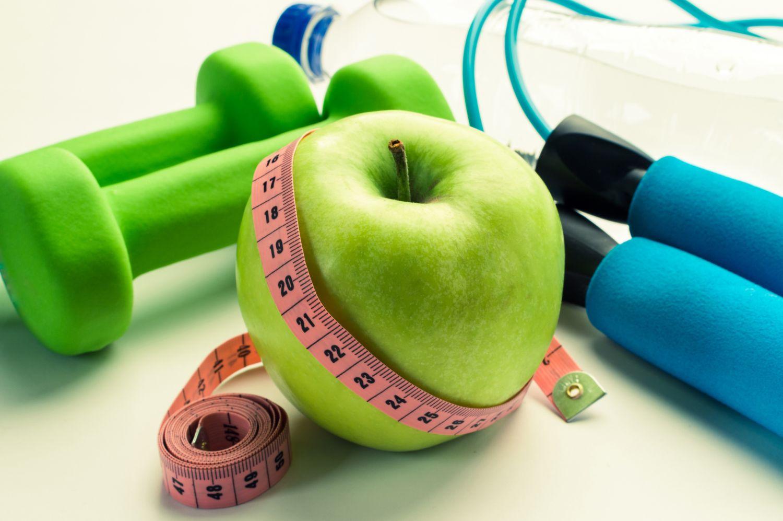 Ein Apfel neben Hanteln. Thema: Schuppenflechte ganzheitlich behandeln