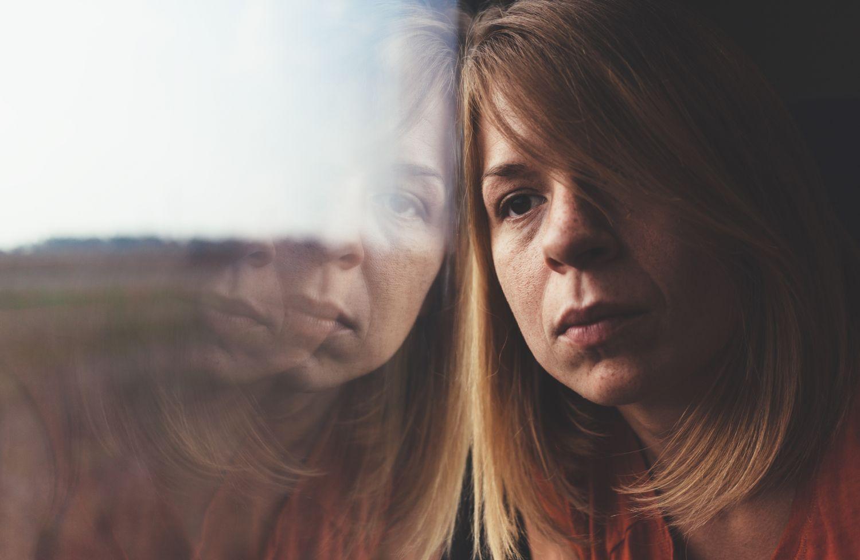 Eine Frau schaut nachdenkend aus dem Fenster. Thema: Schuppenflechte