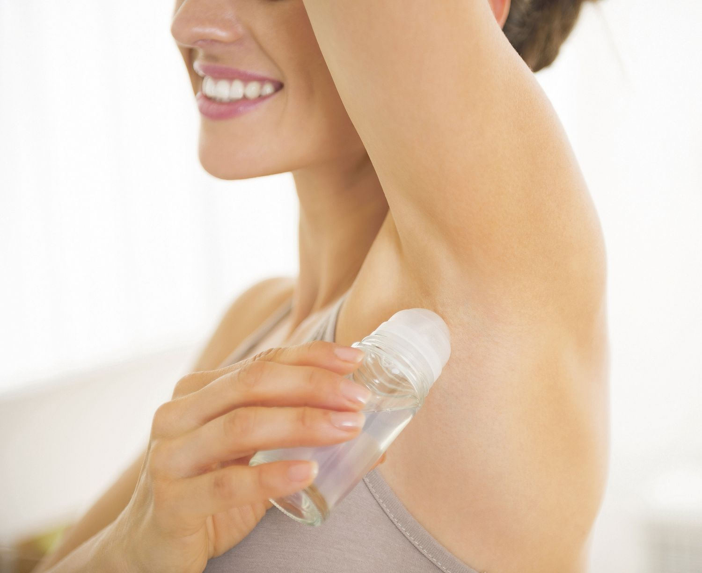 Eine Frau benutzt ein Deodorant.
