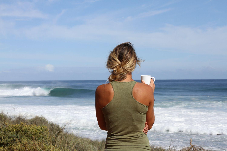 Eine Frau sitzt am Strand in der Sonne - die Ultraviolettstrahlung ist in der Mittagszeit am stärksten.